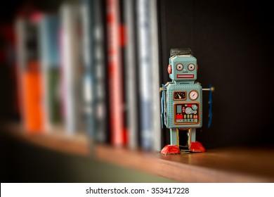 Retro tin toy robot standing on a wooden bookshelf
