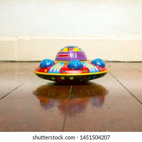 retro tin UFO on old wooden floor  with reflection