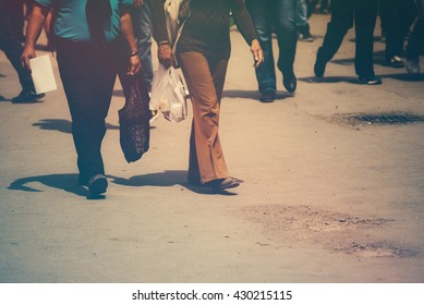 Retro toned image of 1970s look and feel and pedestrians walking the street on a sunny day