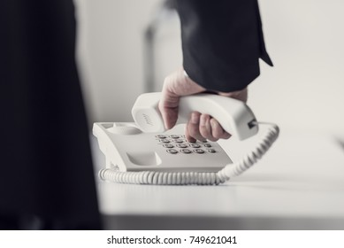 Retro toned image of a businessman dialing telephone number on a classical white landline telephone, low angle view between his arm and body.