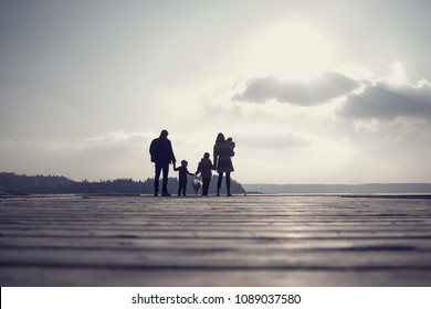 Retro toned image of family with mother, father, two kids and a baby holding hands on a wooden deck overlooking the ocean or lake at sunset.