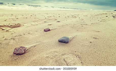 Retro toned nature background made of stones on a beach, shallow depth of field.