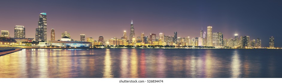 Retro toned panoramic picture of Chicago city skyline at night, USA.