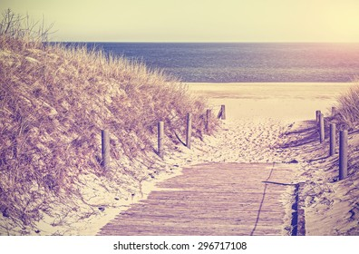 Retro toned photo of a beach path, old film filter applied.