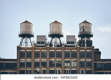 Retro toned picture of three water towers on an old industrial building rooftop, New York City, USA.