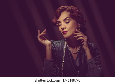 Retro toned portrait of beautiful young woman posing in hollywood style