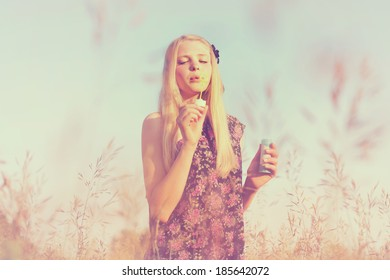 Retro toned portrait of slim young girl making soap bubbles in summer field