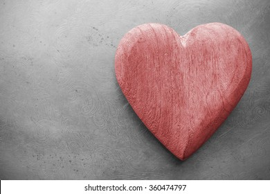 Retro toned wooden heart on grunge background, space for text.