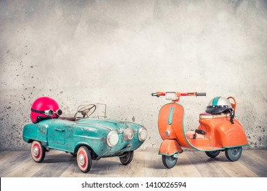 Retro toy antique aquamarine aged pedal car from 60s, red helmet with goggles, classic orange children scooter front loft concrete wall background. Kids race concept. Vintage old style filtered photo