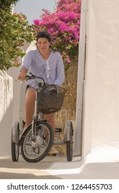 Retro tricycle in a graphic alley at Andros island in Greece with a woman model on top.