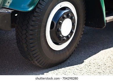 Retro truck wheel, asphalt background. Macro view. soft focus. Old style car part