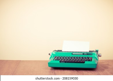 Retro turquoise typewriter on oak wooden table. Old style filtered photo