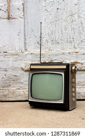 Retro TV as obsolete dusty TV receiver laid on stairs in front of old door outside