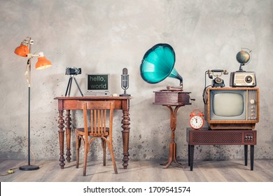 Retro TV, old radio, telephone, alarm clock, globe, gramophone, classic microphone, outdated laptop and camera on wooden table, floor lamp front concrete wall background. Vintage style filtered photo