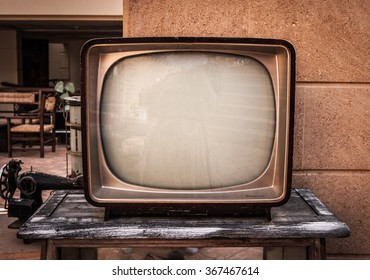 Retro TV, old television on a brick and wood background