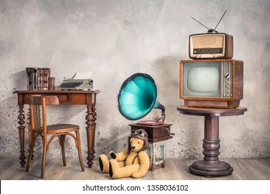 Retro TV receiver, old broadcast radio from circa 50s on wooden table, outdated phonograph, Teddy Bear toy, workplace desk with typewriter, old books and classic chair. Vintage style filtered photo