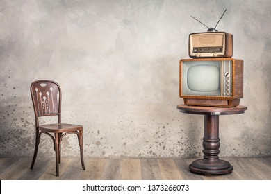 Retro TV receiver and outdated broadcast radio from circa 50s on wooden table and old chair front textured concrete wall background. Vintage style filtered photo