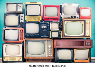Retro TV receivers set from circa 60s, 70s and 80s of XX century, old wooden television stand with amplifier front mint blue wall background. Broadcasting, news concept. Vintage style filtered photo