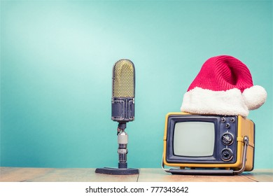 Retro TV in Santa hat and big studio microphone front mint green background. Holidays congratulation in mass media concept. Vintage old style filtered photo