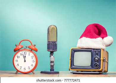 Retro TV in Santa hat, big studio microphone and alarm clock with last minutes to twelve front mint green background. Holidays congratulation in mass media concept. Vintage old style filtered photo