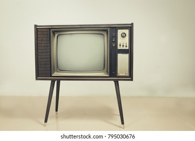 Retro tv with wood case on stand at wall background,Vintage old TV with stand on the floor in the room.