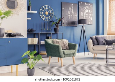 Retro typewriter and golden wall clock in a blue living room interior with paintings and modern furniture