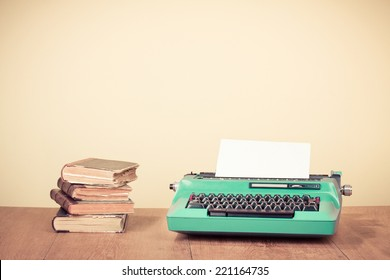Retro typewriter and old vintage books on wooden table near empty wall background