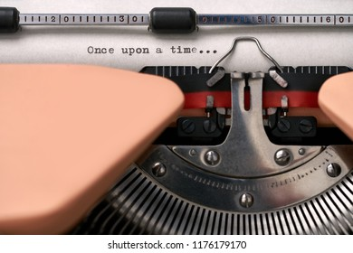 """Retro typewriter with a paper sheet with a printed phrase """"Once upon a time..."""" in the studio. Closeup horizontal photo."""