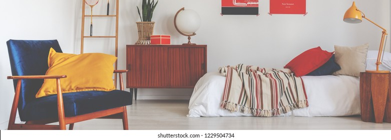 Retro velvet armchair with ochre cushion in real photo of white bedroom interior with vintage cupboard with decor, orange lamp on bedside table and bed with striped coverlet and pillows