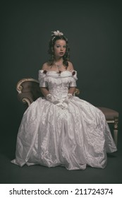 Retro victorian fashion woman wearing white dress. Sitting on antique couch. Studio shot against grey.