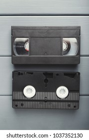 Retro video cassettes on gray wooden background. Top view on front and back sides. Back to the past and multimedia concept, copy space