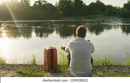 Retro view of only business man with luggage bag is sitting on a river, thinks, and he's looking lake at sunset. Student back after the summer holidays. Concept: relaxing, sadness and solitud