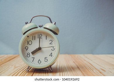 Retro vintage alarm clock on wood table, time concept idea.