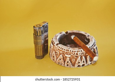 Retro and vintage ashtray and small type cuban cigar, metallic and retro lighter. Isolated yellow background. Smouldering cigarette or cuban cigar.