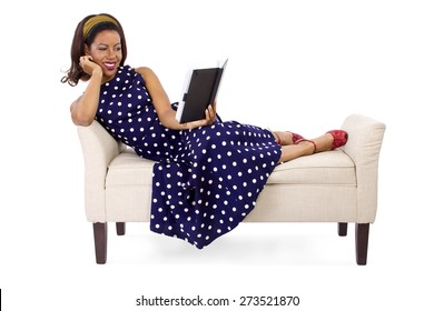 Retro vintage black female reading a book while laying on a chaise.  She is wearing a blue polka dot dress and holding a black book.