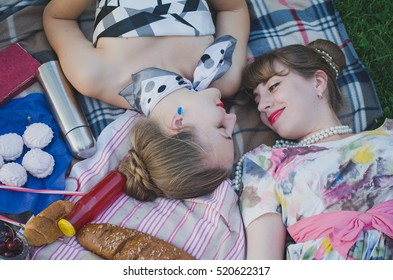 Retro vintage girls having fun in a summer park on a picnic blanket