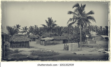 Retro vintage. Old postcard. African village. Houses and barracks with thatched roof with palm trees in background. Rural lifestyle of West Africa. Ghana, village near Atoko