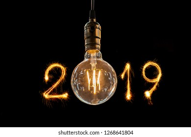 Retro or vintage old style light bulb decor hanging on black background with fire sparkle 2019 for Happy New Year festival greeting concept