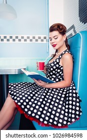 Retro (vintage) portrait of the alluring young girl sitting in cafe and reading book. Pin up style portrait of young girl in dress