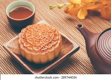 Retro vintage style Chinese mid autumn festival foods. Traditional mooncakes on table setting with teacup.