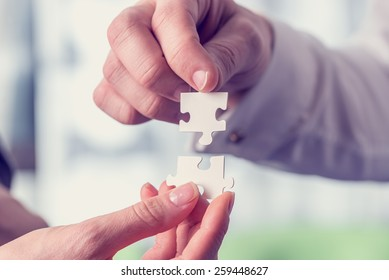 Retro vintage style image of a businesspeople fitting together matching interlocking puzzle pieces conceptual of teamwork and problem solving.