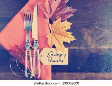 Retro vintage style Thanksgiving table place setting with greeting tag, orange napkin, autumn fall leaves on rustic dark recycled wood background, with copy space.