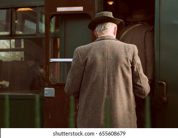 Retro vintage styled photograph of  back view  of older man dressed in a long brown tweed coat climbing into the carriage of an old steam train