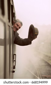 Retro vintage styled photograph of elderly man with mustache  wearing a tweed coat smiling and waving a trilby hat from the window of an old steam powered train engine carriage door