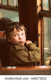 Retro vintage styled photograph of young boy dressed in wwII army clothing looking over his shoulder  sitting by the window  on in the carriage of an old  steam train