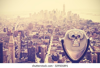 Retro vintage toned tourist binoculars over Manhattan Skyline, New York City, USA.