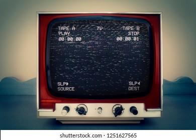 A retro vintage TV screen: a VCR double deck tracking an empty noisy VHS tape. Deep blue background. Heavy analog distortion.