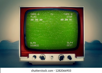 A retro vintage TV showing a green VHS tape screen tracking a noisy signal coming from a double deck. Cool retro vintage backdrop.