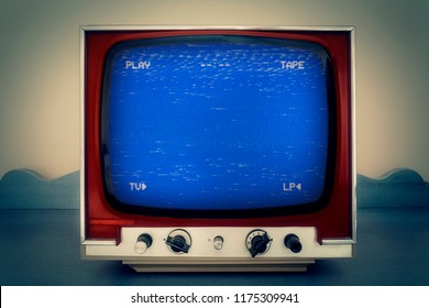 A retro vintage TV showing an old bad broken VHS tape playing. Blue screen with PLAY and TAPE text.
