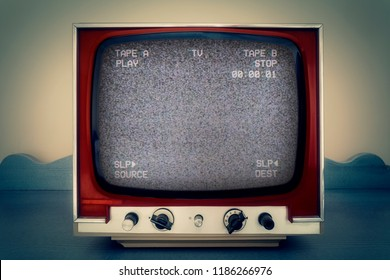 A retro vintage TV showing a VCR double deck tracking an empty noisy VHS tape screen.